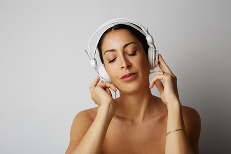 Fashion pretty cool girl half-undressed in white headphones listening to music over empty white background. Relaxing and enjoying concept Stock Photo