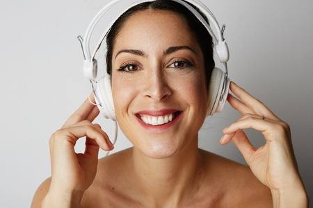 Portrait of fashion smiling cool girl stripped to the waist in white headphones listening to music over empty white background. Relaxing and enjoying concept