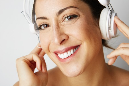 Portrait of fashion happy cool girl stripped to the waist in white headphones listening to music over empty white background. Relaxing and enjoying concept.Closeup Stock Photo