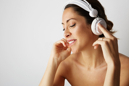 Portrait of fashion happy cool girl topless in white headphones listening to music over empty white background. Relaxing and enjoying concept.Closeup Stock Photo
