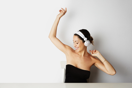 Fashion handsome cool model girl in white headphones listening to music wearing black color dress over white background. Relaxing and free dancing