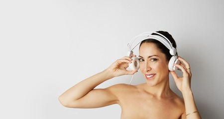 Portrait of fashion happy cool girl topless in white headphones listening to music over empty white background. Relaxing and enjoying concept.Copy paste text space. Wide Stock Photo