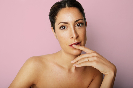 Portrait of happy beauty woman with big brown eyes and dark eyebrows looking camera over empty pink color background.Model with light nude make-up.Healthcare skin concept Stock Photo