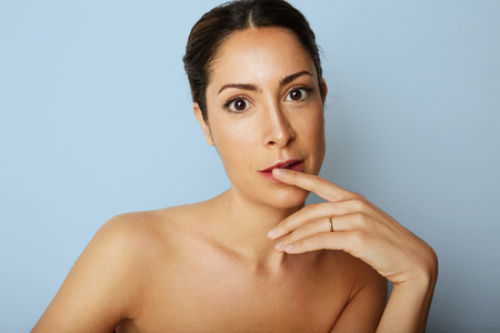 Portrait of romantic beauty woman with big brown eyes and dark eyebrows looking camera over empty blue color background.Model with light nude make-up.Healthcare skin concept Stock Photo