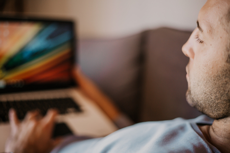 Working moments at home.Young caucasian coworker man in casual clothes working on laptop at sofa at modern apartment. Blurred background