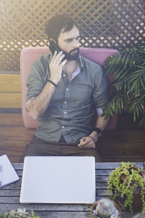 Hipster man working on laptop and using mobile phone while sitting on terrace of cafe. Attractive bearded man calling to friends.Bokeh