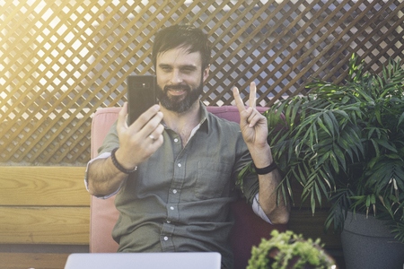 Content attractive man in stylish clothes photographing himself on mobile phone and showing peace gesture.Bearded hipster making selfie via smartphone on terrace outside. Stock Photo