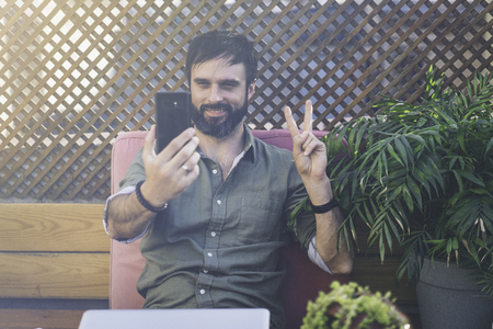 Content confident man in stylish clothes photographing himself on mobile phone and showing peace gesture.Bearded hipster making selfie via smartphone on terrace outside. Stock Photo - 105061973