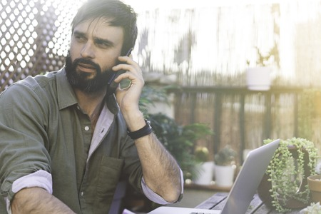 Bearded Man sitting at vintage natural rough wood desk working on laptop computer and using mobile phone at cafe terrace surrounded green flores and cactus.Out of office work concept Stock Photo - 105061975