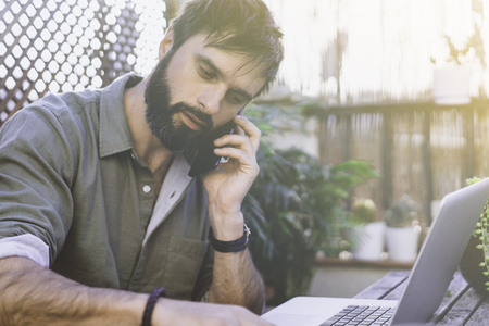 Bearded Man sitting at vintage natural rough wood desk working on laptop computer and using mobile phone at cafe terrace surrounded green flores and cactus.Out of office work concept Stock Photo - 105061976