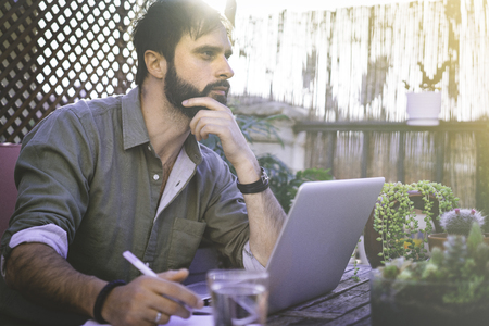 Attractive Bearded Man sitting at vintage natural rough wood desk working on laptop computer at cafe terrace surrounded green flores and cactus.Out of office work concept Stock Photo - 105061978