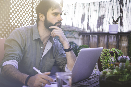 Confident Bearded Man sitting at vintage natural rough wood desk working on laptop computer at cafe terrace surrounded green flores and cactus.Out of office work concept Stock Photo - 105061979