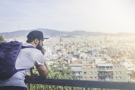 Traveler man looking on a big city, travel and active lifestyle concept.Bearded Tourist Man with backpack enjoy beautiful city view Stock Photo