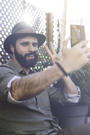Bearded hipster wearing green shirt and brown hat making selfie via smartphone on terrace outside. Positive man relaxing at summer day