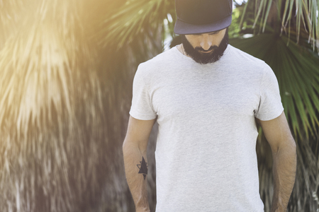 Bearded muscular hipster man model wearing gray blank t-shirt and a black baseball cap with space for your logo or design in casual urban style.Green palm and cactus garden on the background Stock Photo - 105061985