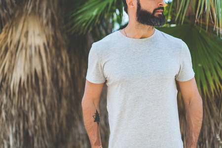 Hipster handsome male model with beard wearing gray blank t-shirt and a black snapback cap with space for your logo or design in casual urban style.Green palm and cactus garden on the background Stock Photo - 105061986