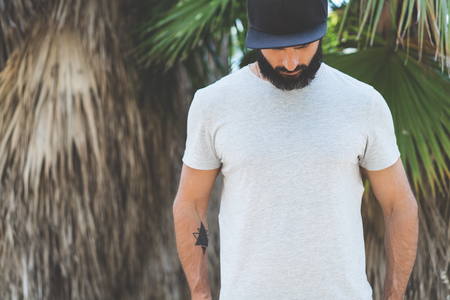 Bearded muscular hipster man model wearing gray blank t-shirt and a black baseball cap with space for your logo or design in casual urban style.Green palm and cactus garden on the background