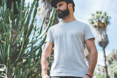 Bearded muscular hipster man model wearing gray blank t-shirt and a black baseball cap with space for your logo or design in casual urban style.Green palm and cactus garden on the background Stock Photo - 105061988