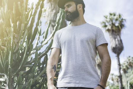 Bearded muscular hipster man model wearing gray blank t-shirt and a black baseball cap with space for your logo or design in casual urban style.Green palm and cactus garden on the background Stock Photo - 105109098