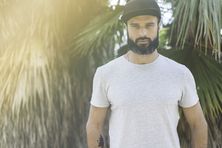 Hipster handsome male model with beard wearing gray blank t-shirt and a black snapback cap with space for your logo or design in casual urban style.Green palm and cactus garden on the background