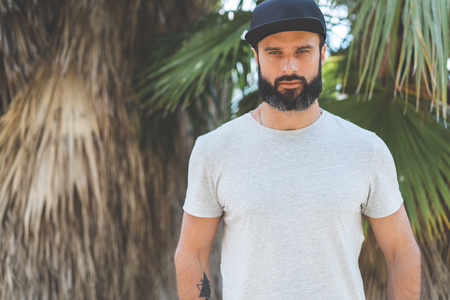 Hipster handsome male model with beard wearing gray blank t-shirt and a black snapback cap with space for your logo or design in casual urban style.Green palm and cactus garden on the background Stock Photo - 105109101