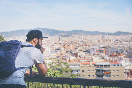 Traveler man looking on a big city, travel and active lifestyle concept.Bearded Tourist Man with backpack enjoy beautiful city view on sunset Stock Photo - 105109103