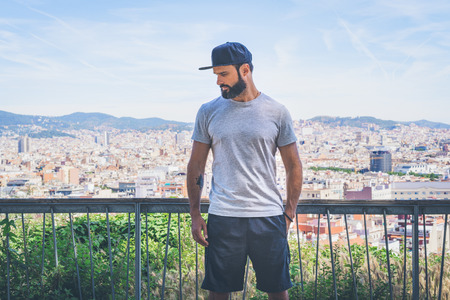 Hipster handsome male model with beard wearing gray blank t-shirt and a black snapback cap with space for your logo or design in casual urban style.Panoramic view of modern BCN city on the background Stock Photo - 105109104
