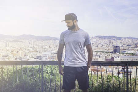 Hipster handsome male model with beard wearing gray blank t-shirt and a black snapback cap with space for your logo or design in casual sport urban style.Panoramic view of modern city on background