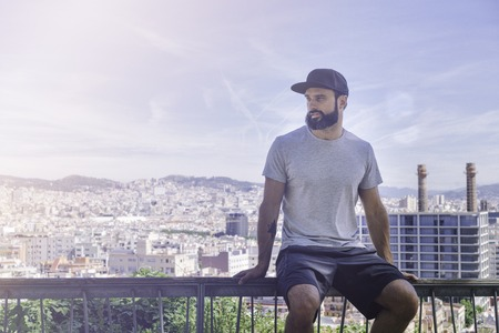 Hipster handsome male model with beard wearing gray blank t-shirt and a black snapback cap with space for your logo or design in casual sport urban style.View of modern europian city on background