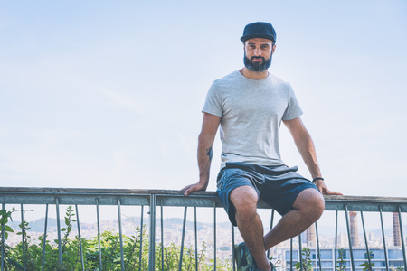 Bearded muscular hipster man model wearing gray blank t-shirt and a black baseball cap with space for your logo or design in casual urban style.Green palm and cactus garden on the background Stock Photo - 105109108