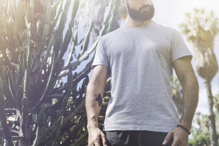 Hipster handsome male model with beard wearing gray blank t-shirt and a black snapback cap with space for your logo or design in casual urban style.Green palm and cactus garden on the background Stock Photo - 105157069