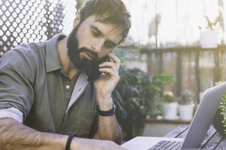Bearded Man sitting at vintage natural rough wood desk working on laptop computer and using mobile phone at cafe terrace surrounded green flores and cactus.Out of office work concept Stock Photo - 105157071