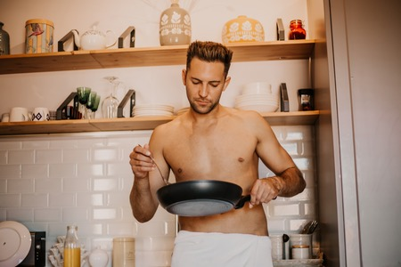 Sexy chef with naked body cooking in the home kitchen Stock Photo - 105157155