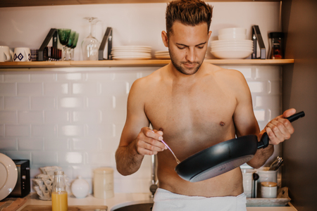 Sexy chef with naked body cooking in the home kitchen Stock Photo