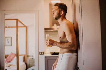 Sexy young man with bare torso holding hand orange juice, looking out the window and smiling while standing in kitchen at home. Stock Photo - 105108184