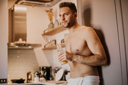 Attrctive young man with bare torso holding hand orange juice, looking out the window and smiling while standing in kitchen at home.