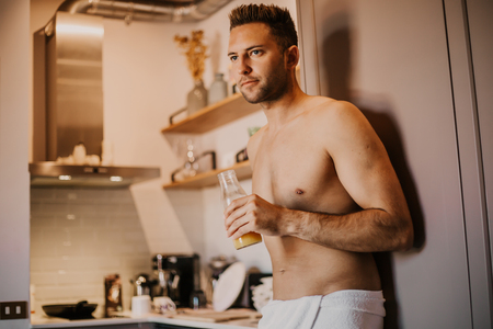 Sexy young man with bare torso holding hand orange juice, looking out the window and smiling while standing in kitchen at home.
