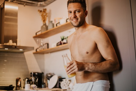 Shirtless hipster man drinking orange juice in the kitchen while leaning on the counter.