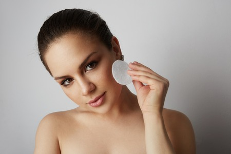 Handsome model girl refreshing skin face with white cotton pads over gray studio background.Model with light nude make-up.Healthcare skin makeup concept