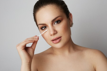 Handsome girl refreshing skin face with white cotton buds over gray studio background.Model with light nude make-up.Healthcare skin makeup concept