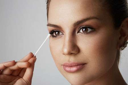 Portrait Handsome beauty girl refreshing skin face with white cotton buds over gray studio background.Model with light nude make-up.Healthcare skin makeup concept Stock Photo