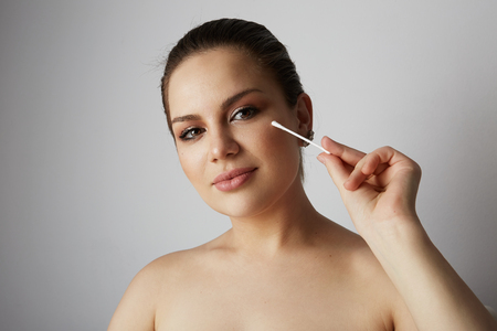Portrait pretty beauty girl refreshing skin face with white cotton buds over gray studio background.Model with light nude make-up.Healthcare skin makeup concept
