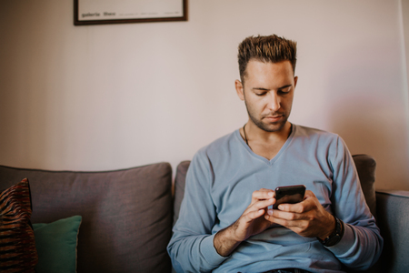 Young handsome man sitting at home on sofa and using mobile phone. Men holding smartphone hands and typing text message Stock Photo