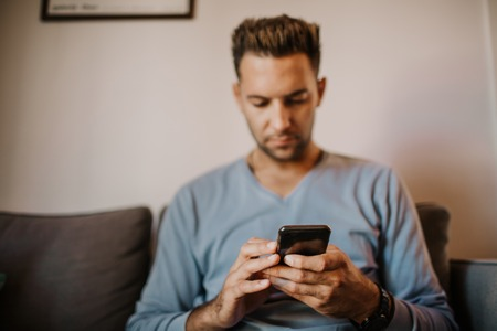 Handsome man using mobile smartphone for surfing web internet and sending audio message. Man using gadget at modern apartment Stock Photo