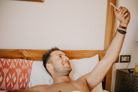 Handsome shirtless muscular bodybuilder man in jeans taking selfie with cell phone while laying on bed. Sexy young man