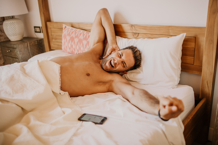 Shirtless sexy male model lying alone on his bed in his bedroom.Carefree guy enjoying new day Stock Photo