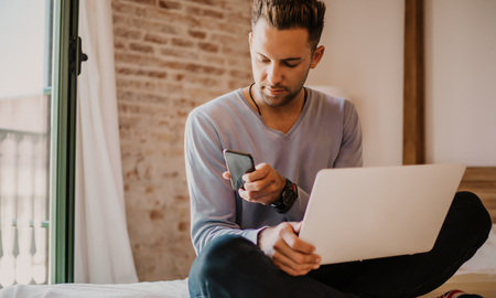 Working moments at home.Young caucasian coworker man in casual clothes working on laptop at modern apartment. Blurred background Stock Photo - 105061561