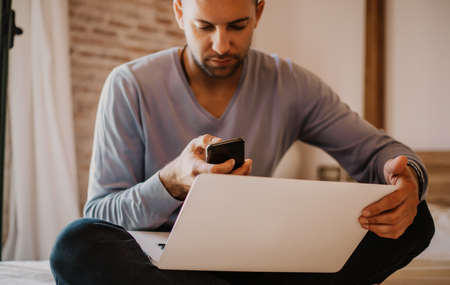 Working moments at home.Young caucasian coworker man in casual clothes working on laptop at modern apartment. Blurred background Stock Photo - 105061563