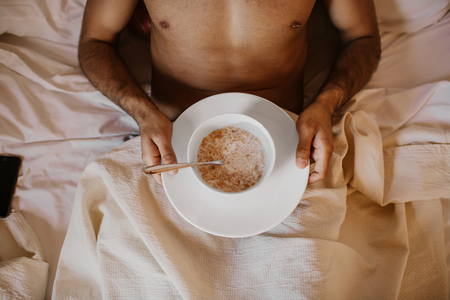 Handsome man lying on bed with healthy breakfast in the morning. Attractive guy smiling in bedroom at home, sexy young male model Stock Photo - 105687247