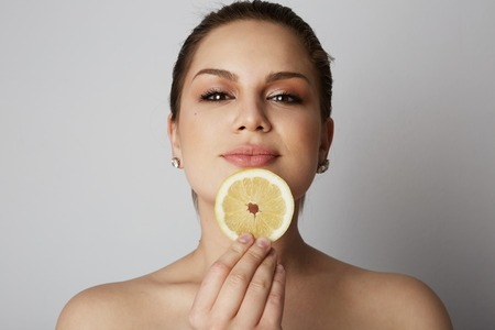 Beauty women with big eyes and dark eyebrows holding hand fresh limon close her lips over gray background.Model with light nude make-up, color studio background Stock Photo - 105061577